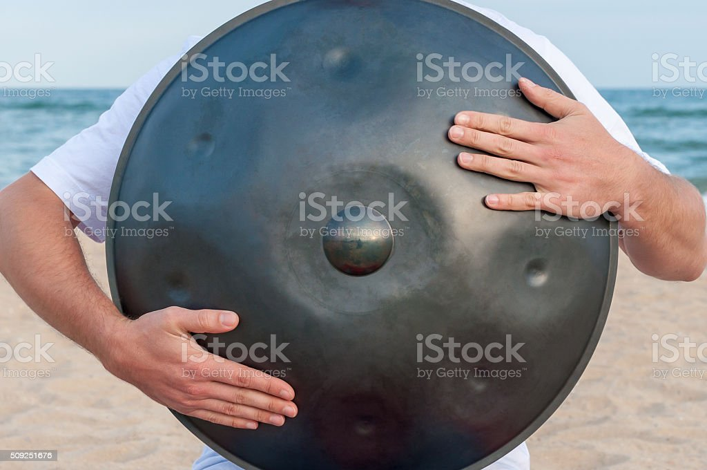 Busker on the sand beach and holding a handpan or stock photo