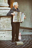 Busker playing an accordion on the street in Rome, Italy