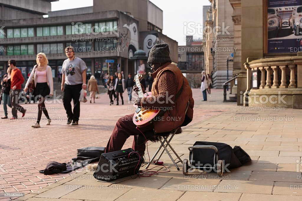 Busker playing guitar in Birmingham city center stock photo