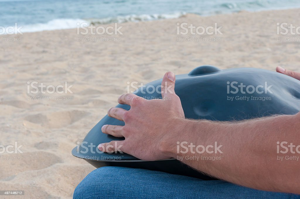 Busker sit on sand and play the Hang or handpan stock photo