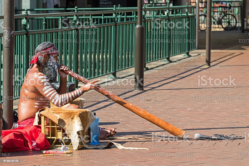 Busker sitting and blowing didgeridoo, Australian Aboriginal musical instrument, Australia stock photo