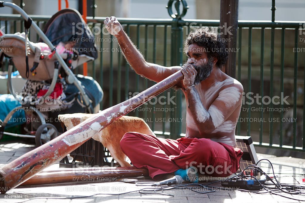 Busker sitting and blowing didgeridoo stock photo