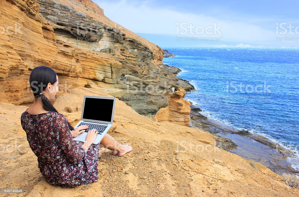 Bussines woman working on the mountain with a laptop stock photo
