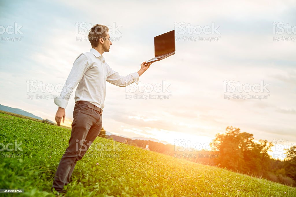 Bussinesman holding computer in the air , outside in nature stock photo