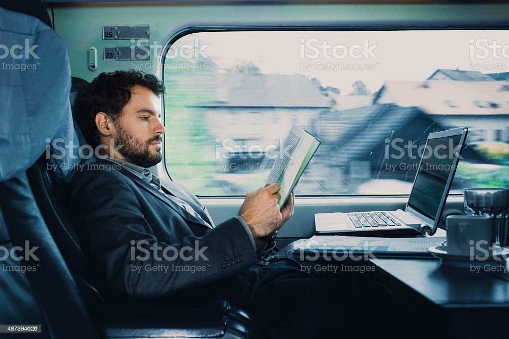 . bussinesman seating on a train  beside  window  and reading stock photo