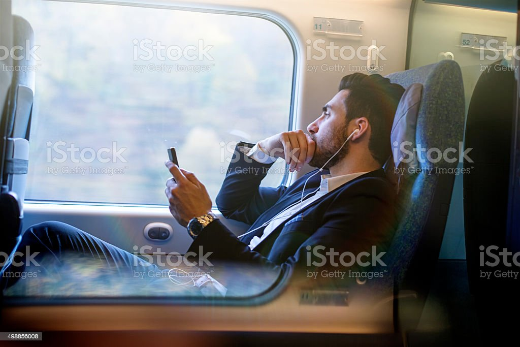 Bussinesman seating on a train beside window and working stock photo