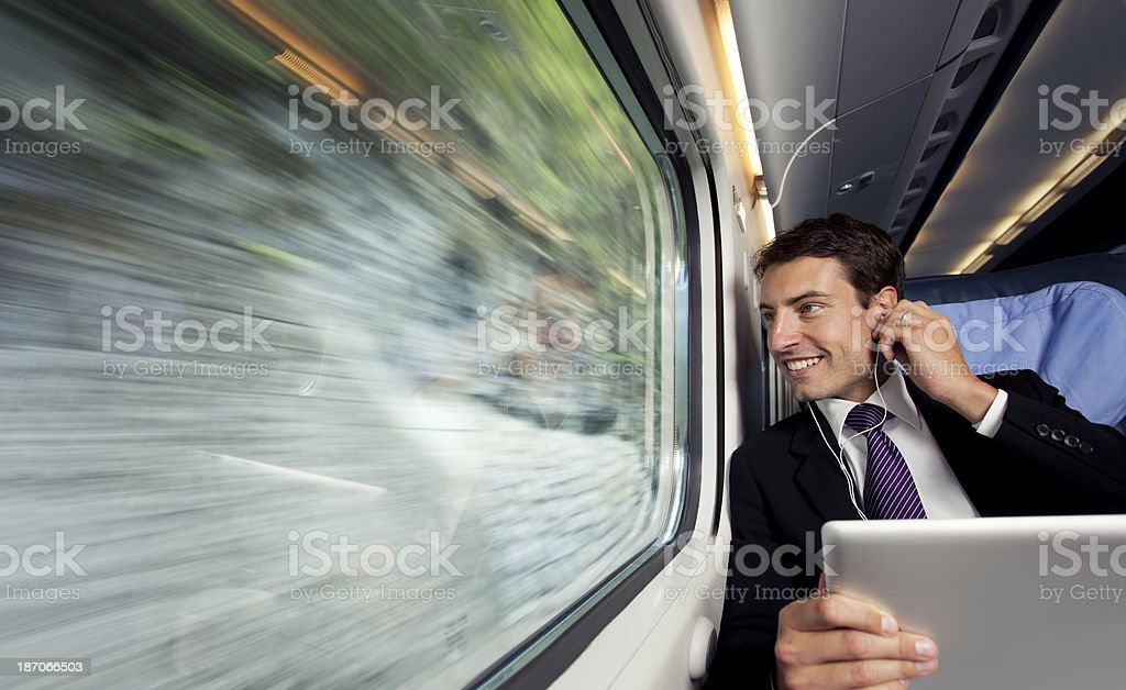 bussinesman seating on a train  lisenig music trough digital table stock photo