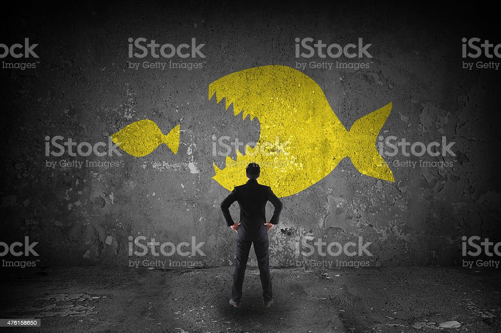 bussiness look at a big fish eating little fish stock photo