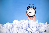 bussiness problems for help:hand holding clock in crumpled papers