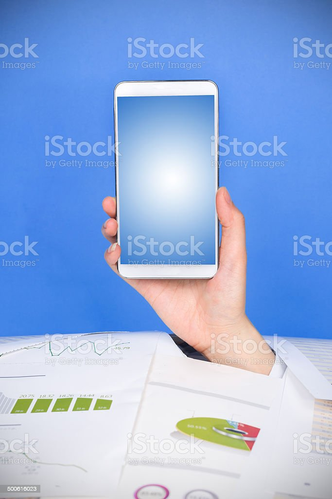 bussiness problems:hand holdling smartphone in crumpled pile of papers stock photo