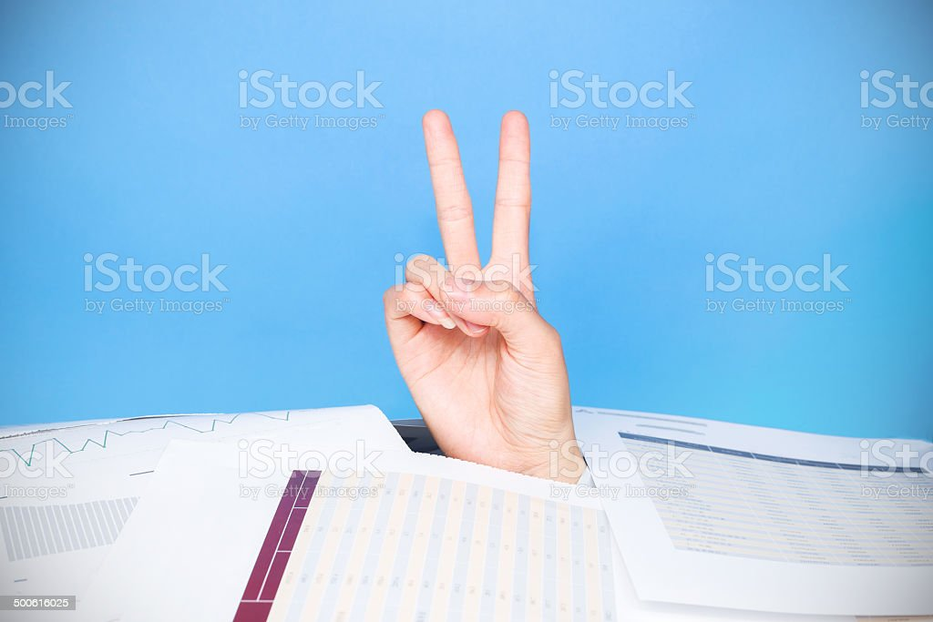 bussiness problems:victory hand sigh in crumpled pile of papers stock photo