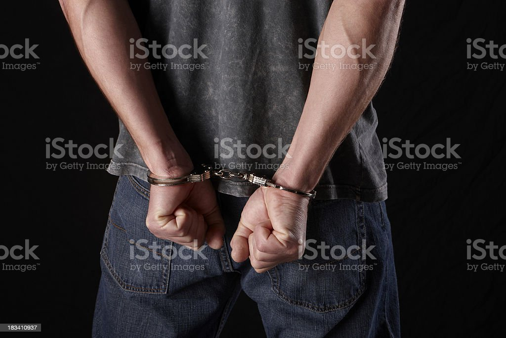 Busted, Man in hand cuffs stock photo