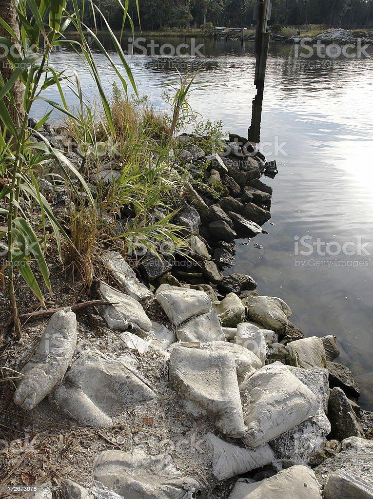 Busted Sand Bags On The River Bank stock photo