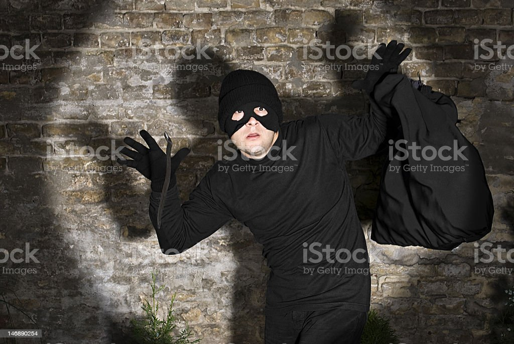 Busted thief, police light around him stock photo