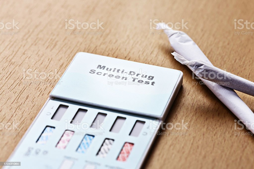 Busted! Two marijuana joints next to home drug test kit stock photo