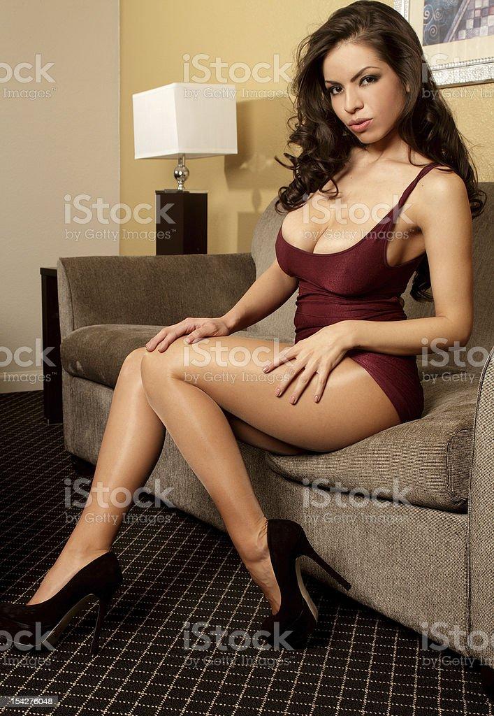 Busty Latina glamour model in tight maroon dress stock photo