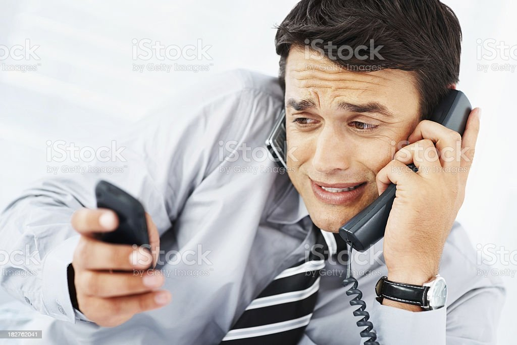 Busy business man attending many phone calls simultaneously royalty-free stock photo