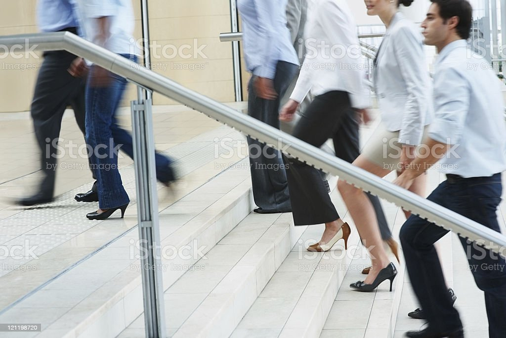 Busy business people ascending on office stairs stock photo