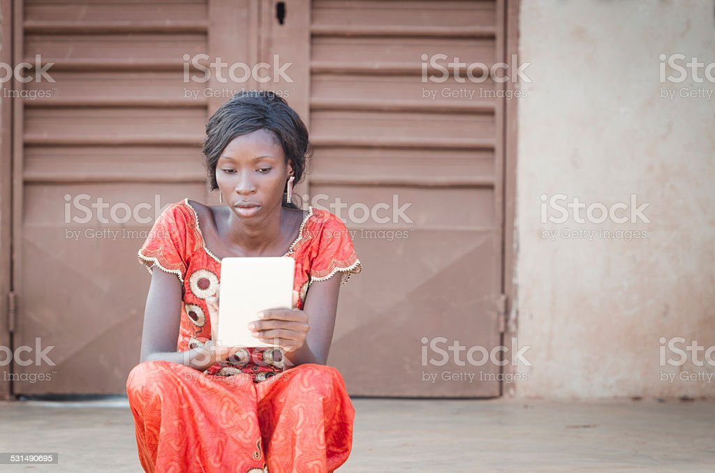 Busy Business Woman Symbol: Young African Girl Reading Tablet PC stock photo