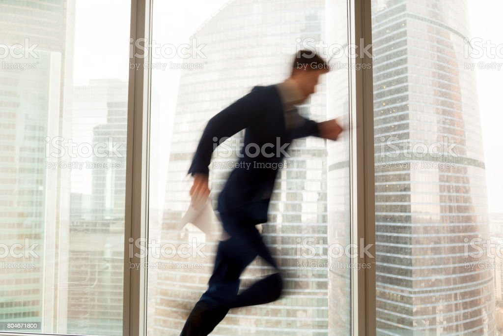 Busy businessman hurrying up, getting late, city view, motion blur stock photo