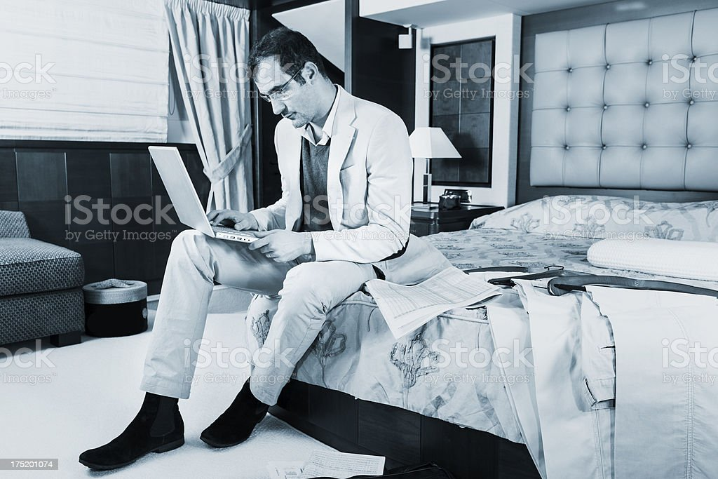 Busy businessman reading e-mails on laptop. Luxurious hotel room royalty-free stock photo