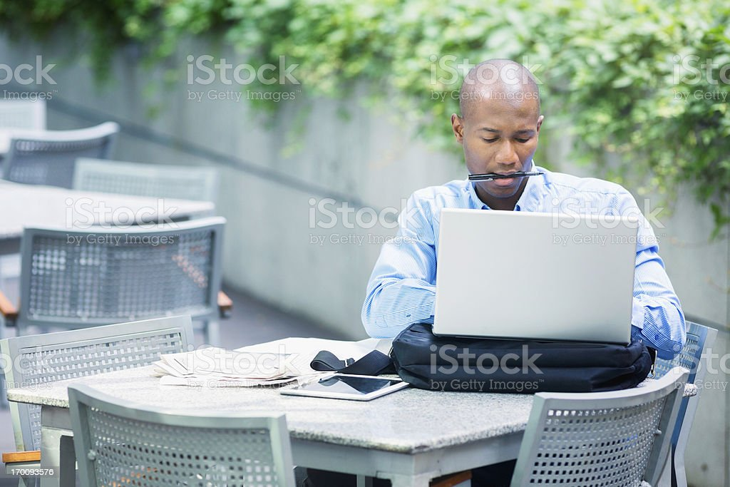 Busy businessman typing on laptop outdoors royalty-free stock photo