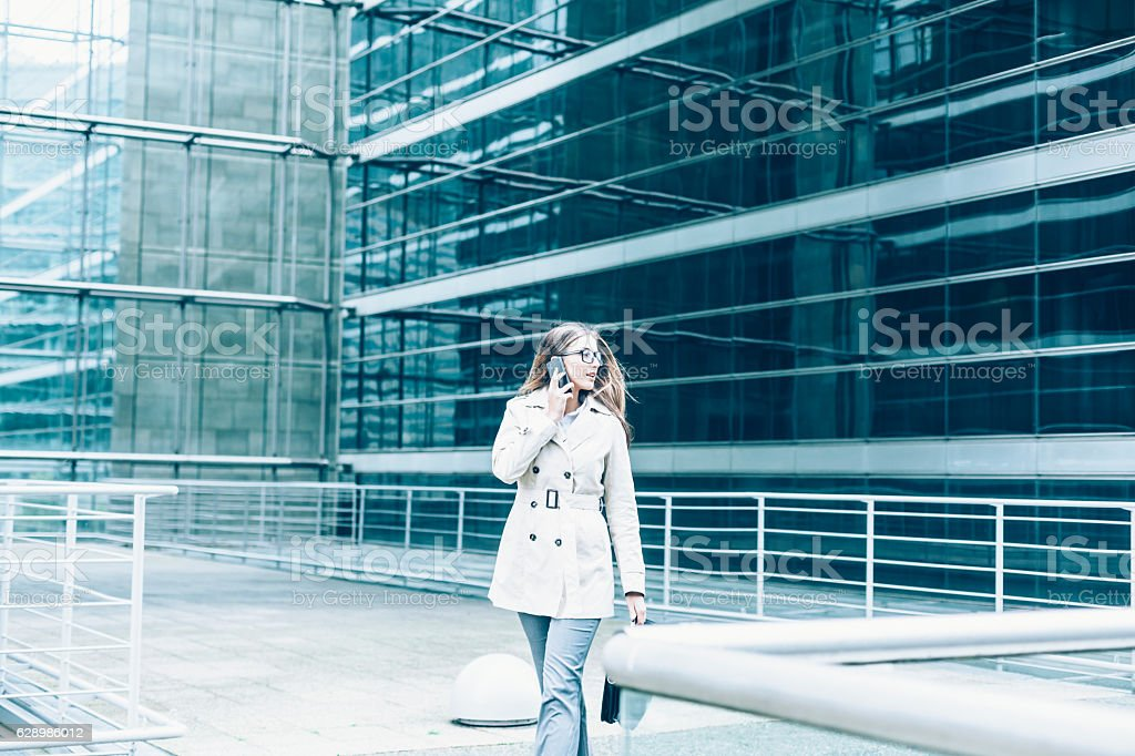 Busy businesswoman walking on street and talking on smart phone stock photo