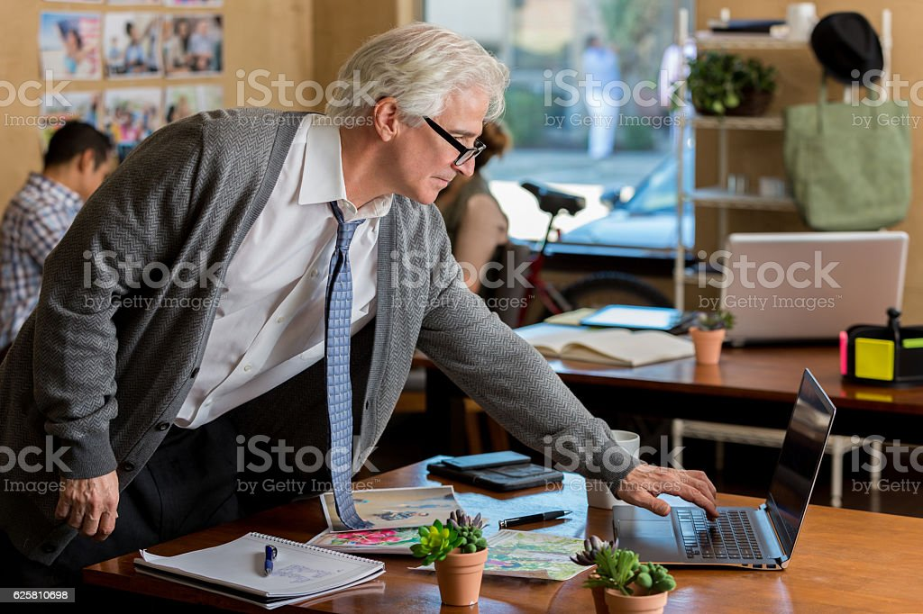 Busy Caucasian senior businessman looks at laptop at work stock photo