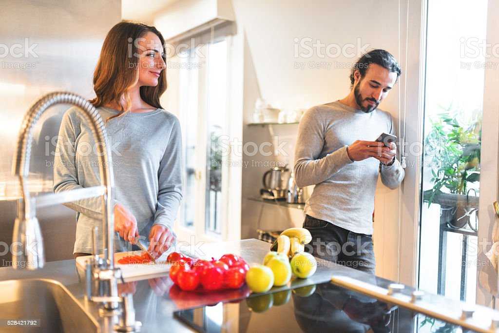 busy couple cooking in the kitchen stock photo