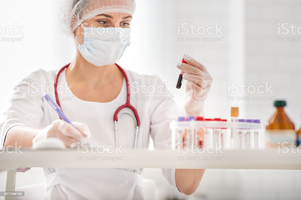 Busy doctor scrutinizing test tubes stock photo