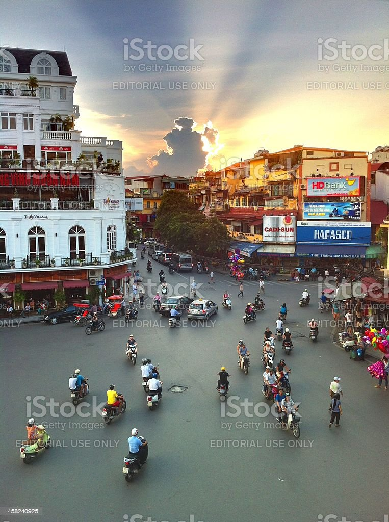 Busy intersection traffic in Hanoi, Vietnam at sunset stock photo