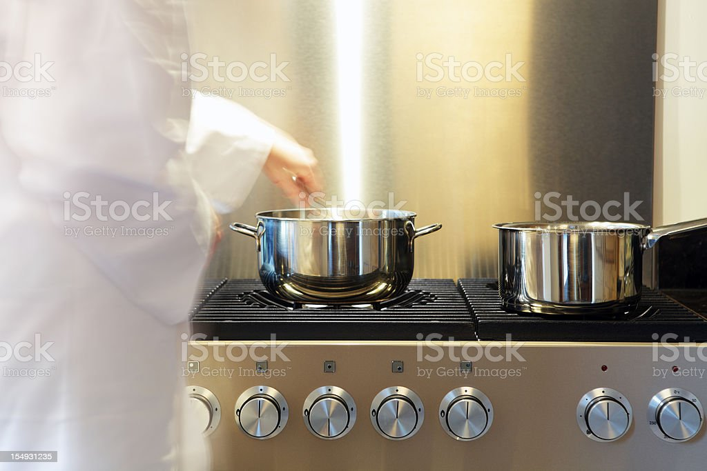 Busy Kitchen Stove with Pans and Chef royalty-free stock photo