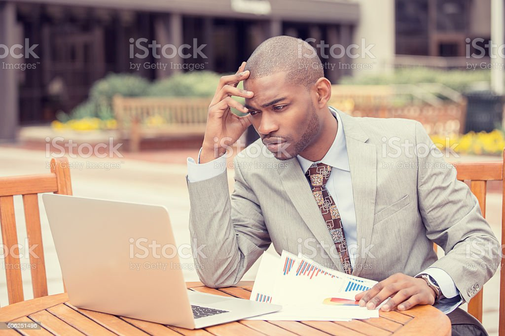 Busy man analyzing company financial report balance sheet statement stock photo