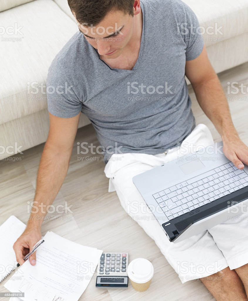 Busy man sitting on floor and using a laptop royalty-free stock photo