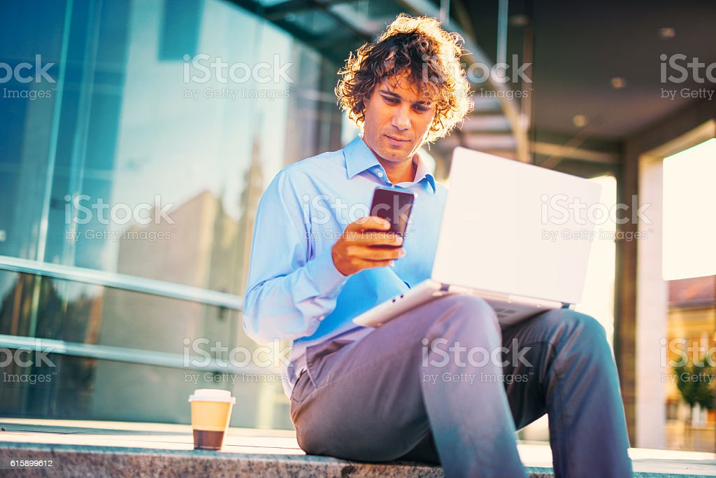 Busy man using access to public wi-fi stock photo