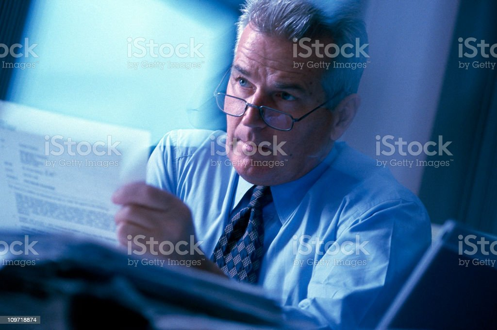 Busy mature (50s) executive in action in office setting. stock photo