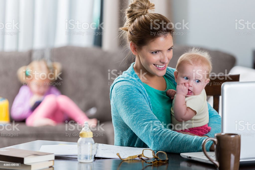 Busy mom holds daughter while working stock photo