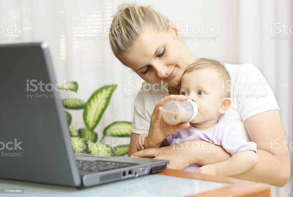 Busy mother feeding baby royalty-free stock photo
