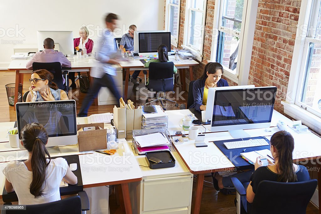 Busy office setting with employees at computers stock photo