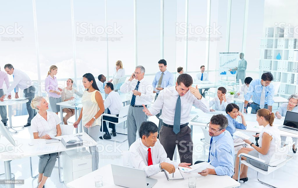 Busy office with workers stressed out stock photo