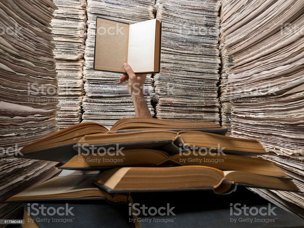 Busy reader needs help, raising his hand among books, documents stock photo