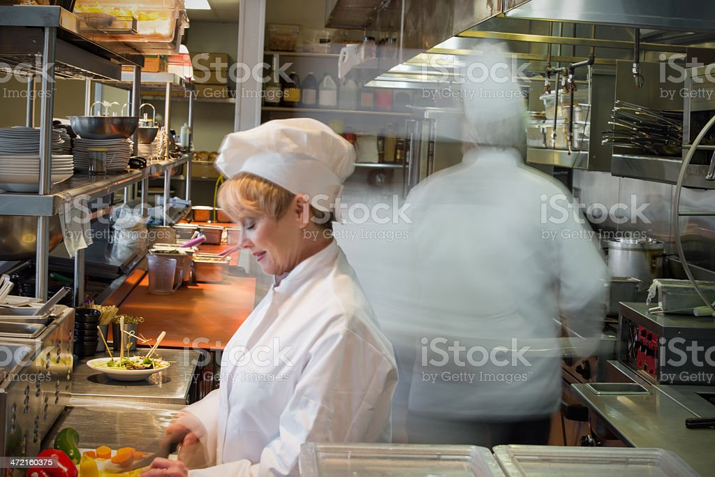Busy restaurant chefs cooking in commercial kitchen, with motion royalty-free stock photo