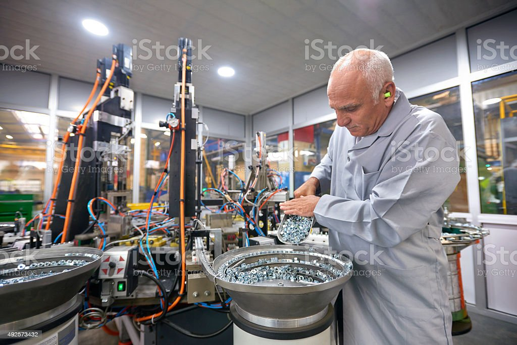 Busy worker in bolt factory stock photo