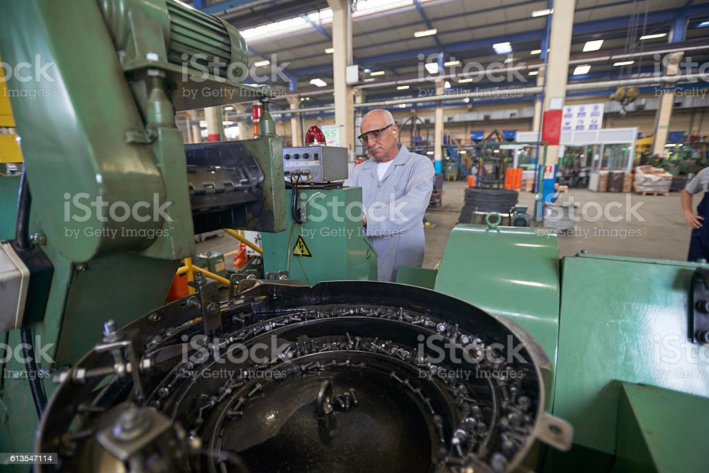 Busy Senior Worker In Bolt Factory stock photo