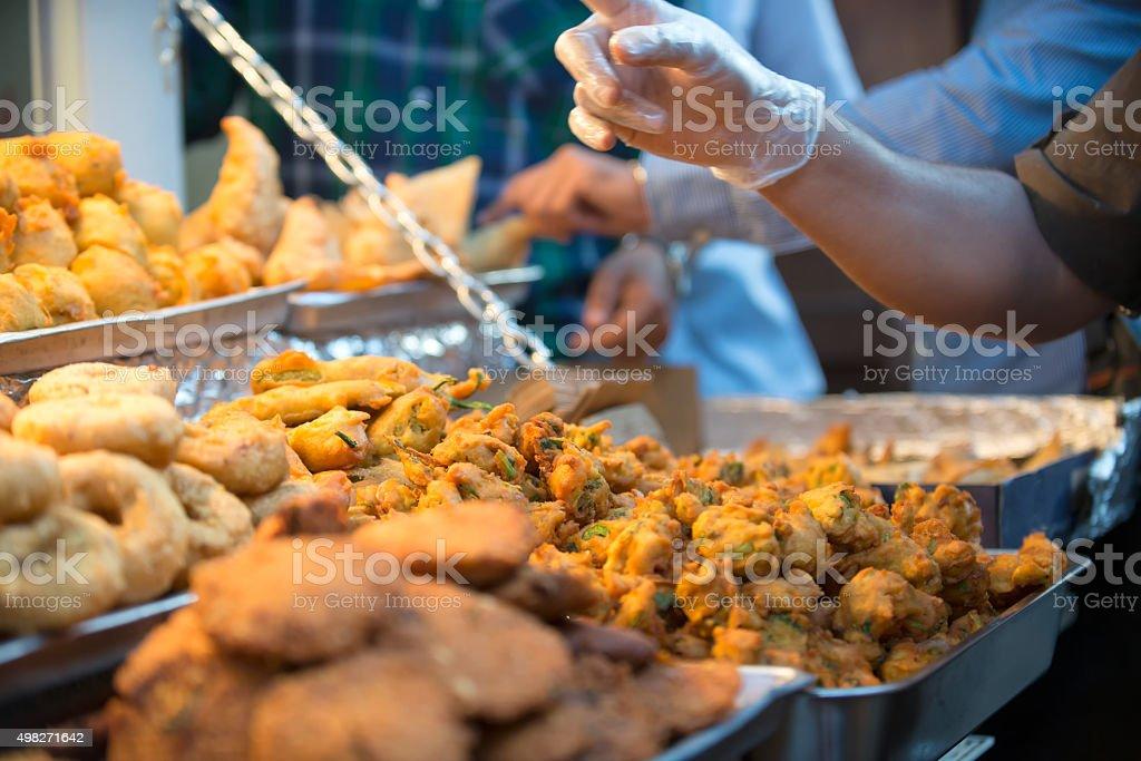 Busy Street Food Vendor Selling Indian Pakoras, Samosasa and Snacks stock photo