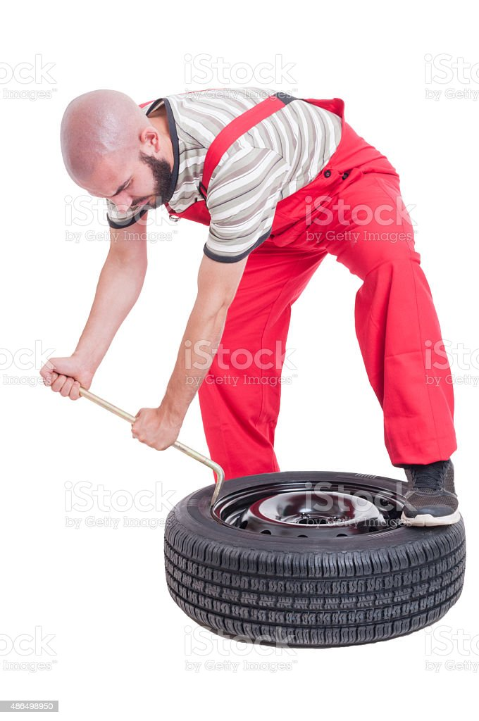 Busy vulcanization mechanic changing car tire stock photo