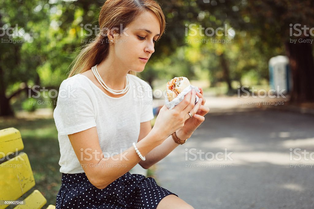 Busy woman eating hamburger outside the office stock photo
