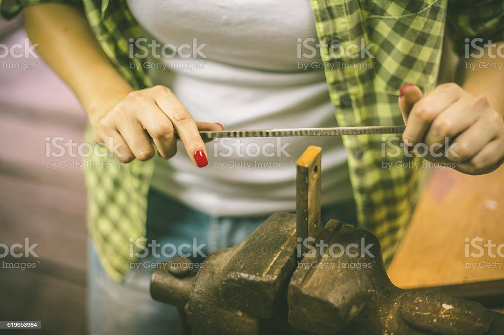 Busy woman tinkering in workshop. stock photo