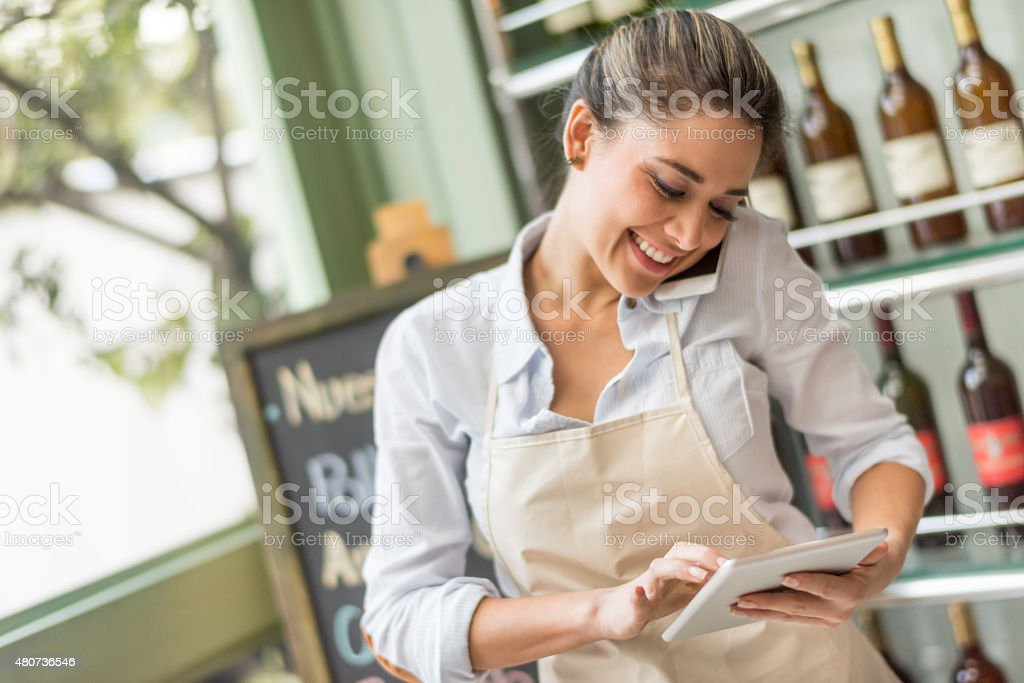 Busy woman working at a restaurant multitasking stock photo