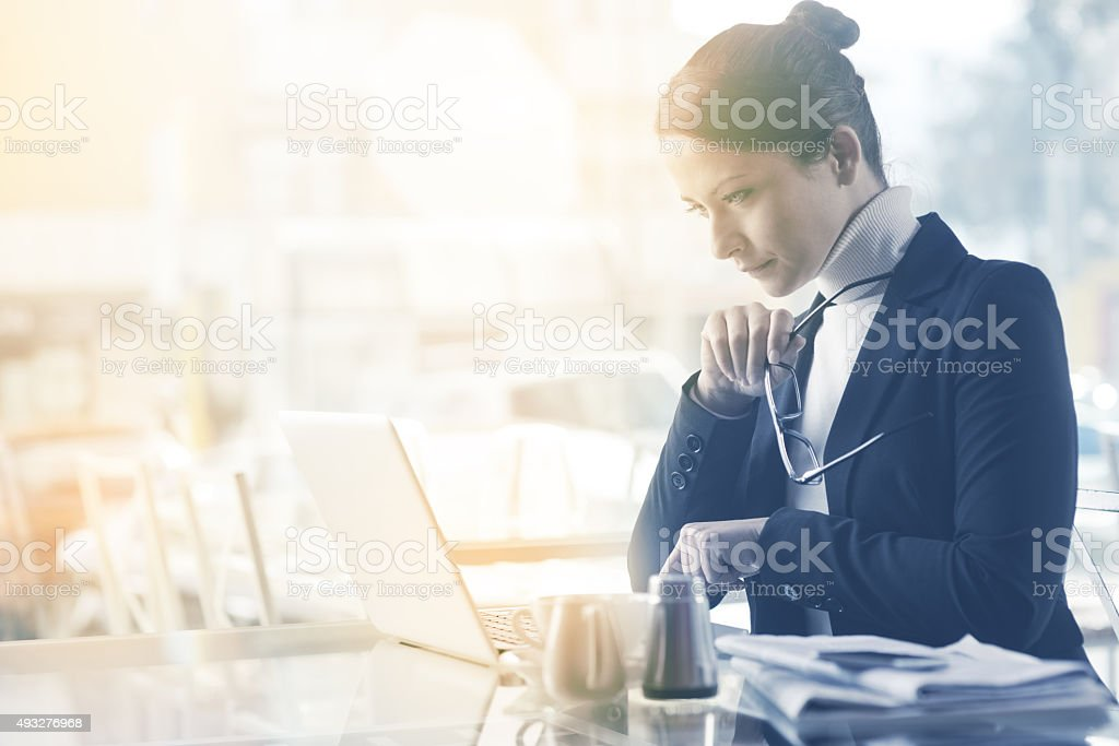 Busy woman working with her laptop stock photo